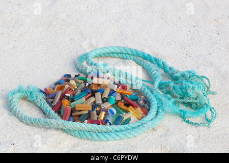 Cigarette lighters and rope, marine debris washed ashore on a pacific island then collected by tourists to prevent - Stock Photo