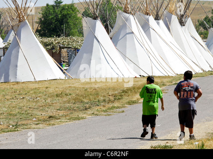 Two young Native Americans walking along a row of teepees on the Crow reservation in Montana. - Stock Photo