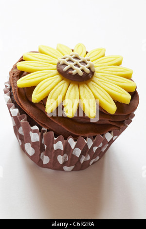 Chocolate cupcake with yellow marzipan daisy flower on top isolated on white background - Stock Photo