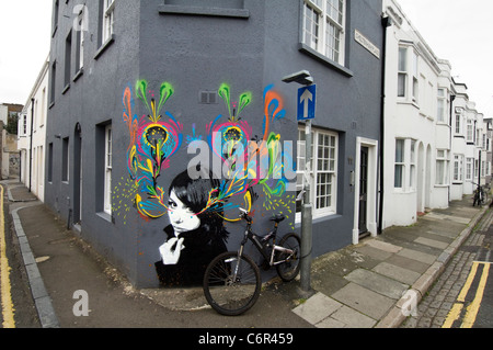 Graffiti of a girl by Hutch and Stinkfish spray painted on a terrace house in North Laine, Brighton, East Sussex, - Stock Photo