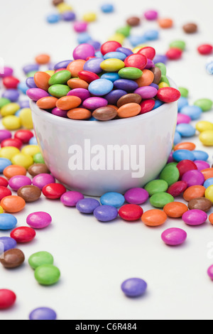 Smarties in a white bowl on a white background. - Stock Photo