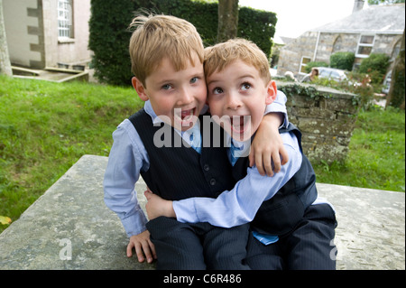 Six year old twin boys in smart wedding suits, hugging each other - Stock Photo