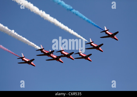British RAF 'Red Arrows' display team, flypast of Hawk T1 jets with colourful red, white and blue [vapour trails], - Stock Photo