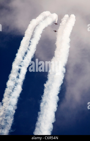 'Red Arrows' white [vapour trails] against blue sky, England, UK - Stock Photo