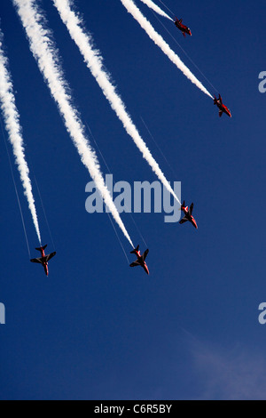 'Red Arrows' aerobatic display team, Hawk T1 jets and white [vapour trails] against blue sky, England, UK - Stock Photo