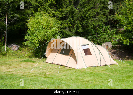 A tent on a campsite in the woods - Stock Photo