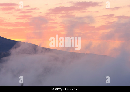 Early morning mist over a valley - Stock Photo