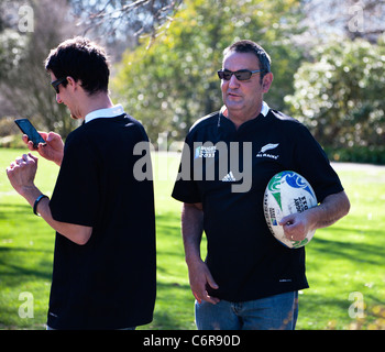 Two rugby world cup 2011 supporters wearing New Zealand All Blacks shirts. One holding a souvenir World Cup rugby - Stock Photo