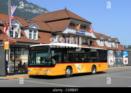 Yellow Swiss postbus waiting outside Interlaken Ost (East) railway station with a service to Interlaken West, Switzerland. - Stock Photo