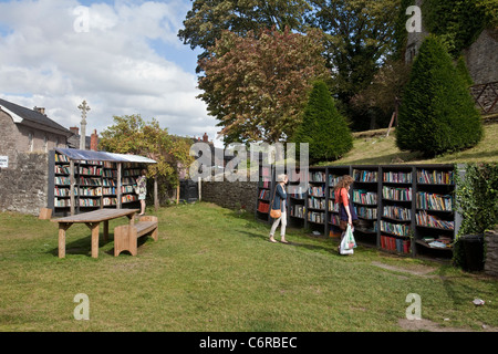 Two people browsing at an honesty bookshop in the grounds of Hay Castle in Hay-On-Wye, UK - Stock Photo