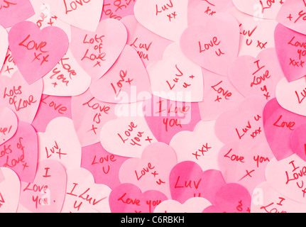 Messages of Love written on pink heart shaped Post-it note paper - Stock Photo