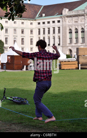 man on a slackline in the park of vienna's hofburg - Stock Photo