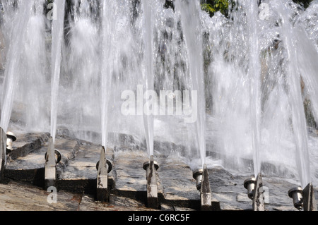 Seven fountains in a row spraying water - Stock Photo