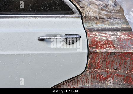 Vintage car window and scraped metal door with raindrops. Background texture. - Stock Photo