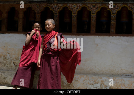 Two very young apprentice monks giggle in front of a bank of prayer wheels at the Wangduephodrang Dzong monastery - Stock Photo