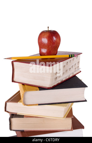 Stack of colorful hardbound books stacked vertically with a red apple and yellow pencil on the top book. - Stock Photo