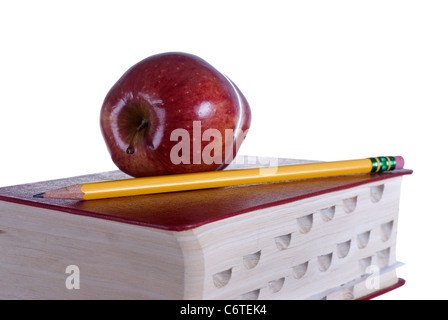 A red apple and pencil sitting on a red book isolated against a 255 white background. - Stock Photo