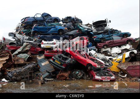 Scrap cars in a scrap metal yard which will be crushed and recycled. - Stock Photo