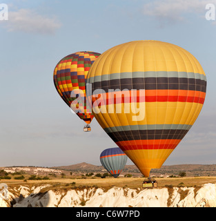 three multi colored hot air balloons low level flight over Cappadocia cliffs, early morning sun, square format, - Stock Photo