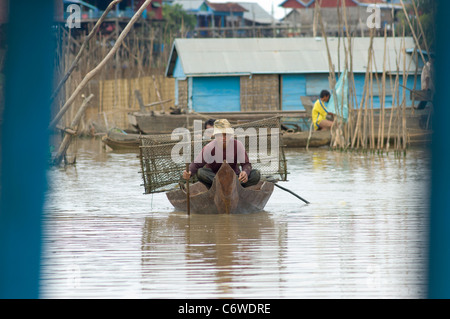 Fishing boat with fishing baskets in a tributary of Tonle Sap lake, at Kompong Klang village near Siem Reap, Cambodia - Stock Photo