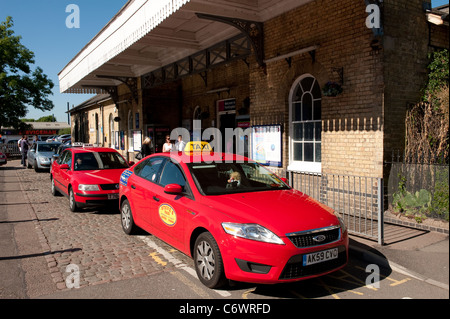Taxis queuing to collect customers outside Huntingdon Railway Station, Cambridgeshire, England. - Stock Photo