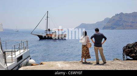 Santorini Cyclades Islands, Greece, Asian couple waiting a tourist boat in Fira - Stock Photo