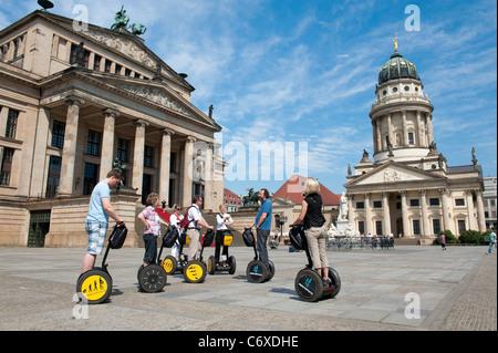 Tourists on segway tour in Gendarmenmarkt square and Konzerthaus and Franzosischer Dom in Mitte district of Berlin - Stock Photo