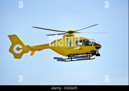 A helicopter of the Strathclyde Police force coming in to land against a clear blue sky - Stock Photo