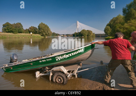 Men loading boat on trailer at Oder river near Redzinski Bridge in Wroclaw, Lower Silesia, Poland - Stock Photo