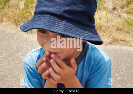Curious boy touching his mouth - Stock Photo