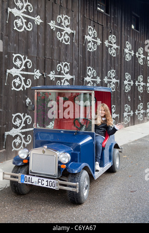 Blond girl driving funny little classic car - Stock Photo