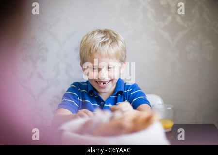 Boy smiling at dinner table - Stock Photo