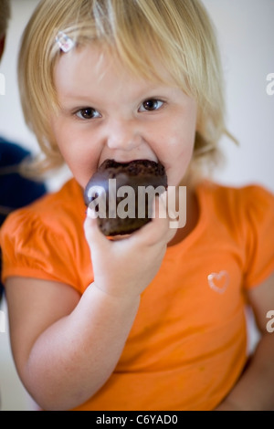 Toddler girl eating chocolate muffin - Stock Photo