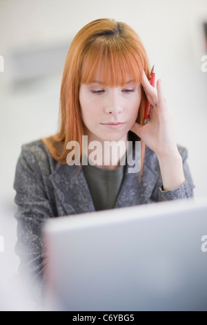 Stressed businesswoman working in office - Stock Photo