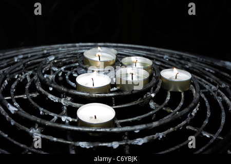 Offertory or Prayer Candles burning in remembrance of loved ones in a Catholic church. - Stock Photo