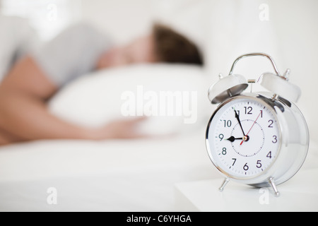 Close up of alarm clock on bedside table - Stock Photo