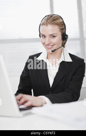 Businesswoman in headset using laptop - Stock Photo