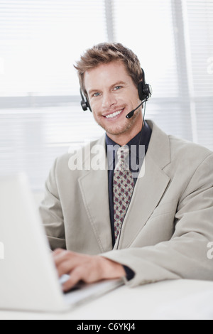 Businessman in headset using laptop - Stock Photo