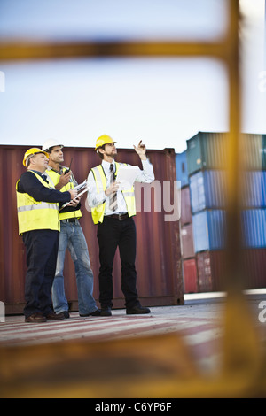 Workers talking in shipping yard - Stock Photo