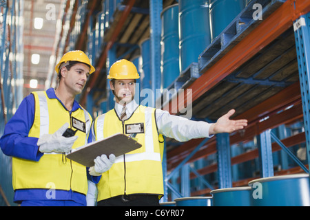Workers with containers in warehouse - Stock Photo