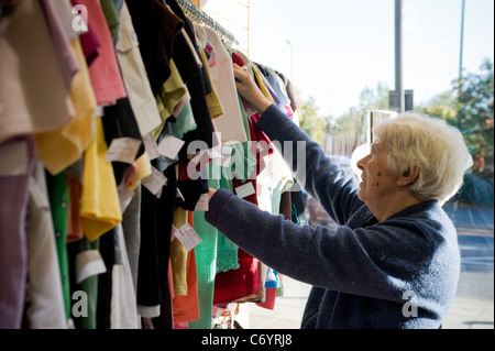 An old lady looking through clothes in the St Luke's hospice charity shop in the London borough of Harrow - Stock Photo