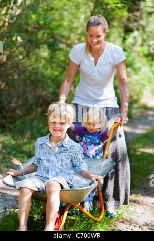 Mother pushing children in wheelbarrow - Stock Photo