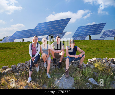 People sitting on wall by solar panels - Stock Photo