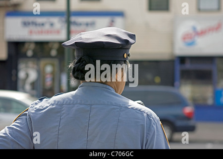 A New York City police officer patrols a section of Brooklyn in the afternoon. - Stock Photo