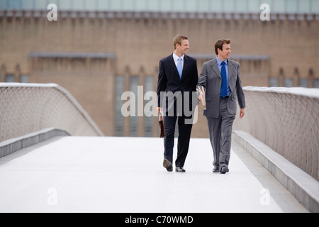 Businessmen walking on bridge together - Stock Photo