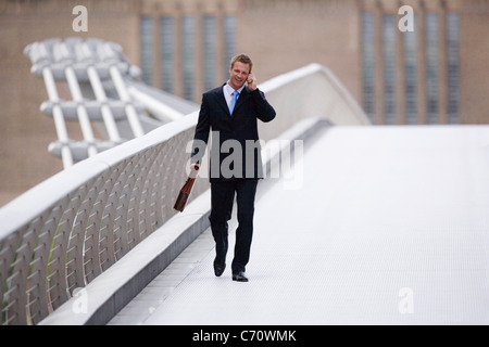 Businessman on cell phone outdoors - Stock Photo