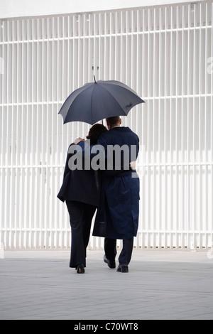 Couple walking under umbrella - Stock Photo