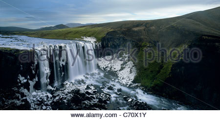 Freezing waterfall surrounded by ice - Stock Photo