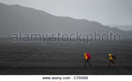 Hikers walking in rural landscape - Stock Photo