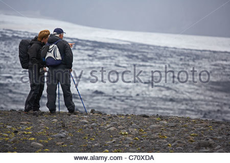 Hikers overlooking snowy landscape - Stock Photo